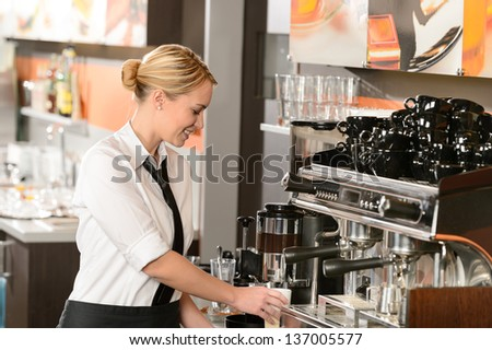 Smiling waitress preparing hot beverage in coffee house - stock photo