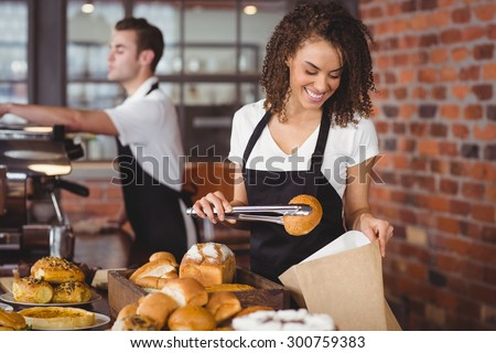 Smiling waitress putting bread roll in paper bag at coffee shop - stock photo