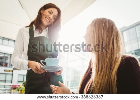 Smiling waitress serving a coffee to customer - stock photo