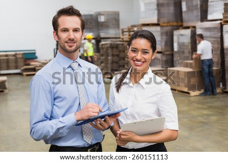 Smiling warehouse managers working together in a large warehouse - stock photo
