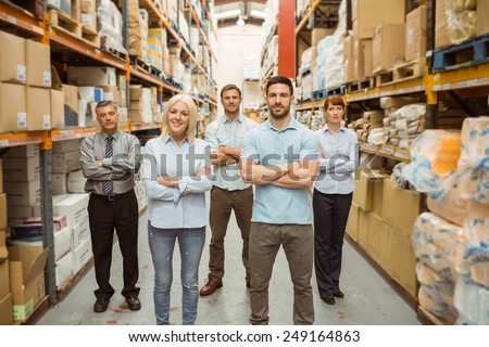 Smiling warehouse team with arms crossed in a large warehouse - stock photo