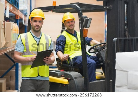 Smiling warehouse worker and forklift driver in warehouse - stock photo