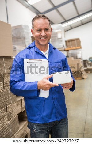 Smiling warehouse worker holding small box and clipboard in a large warehouse - stock photo