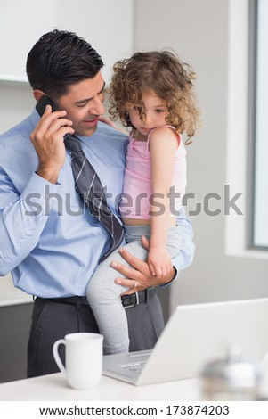 Smiling well dressed father using cellphone while carrying his little daughter in the kitchen at home - stock photo