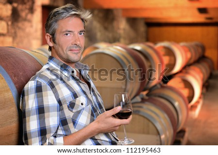 Smiling winemaker standing in wine cellar with glass - stock photo