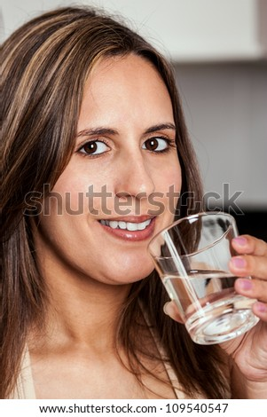 Smiling Woman about to drink a glass of water - stock photo