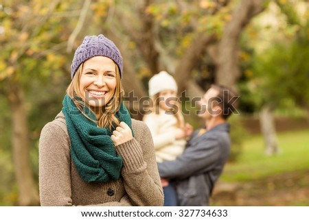 Smiling woman against her husband and her daughter on an autumns day - stock photo