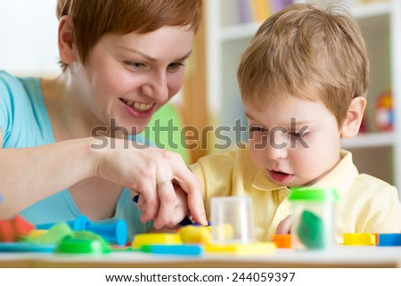 smiling woman and  child boy play colorful clay toy at playschool or home - stock photo