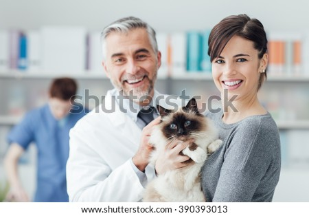 Smiling woman and her cat at the veterinary clinic, a doctor is examining the pet - stock photo