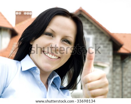 smiling woman and house in the background - stock photo