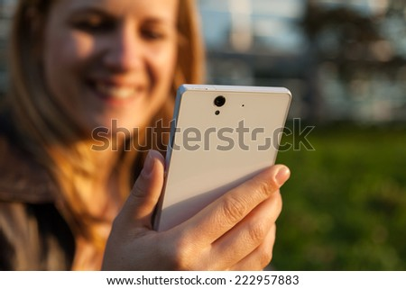 smiling woman and white smarpthone in sunlight - stock photo
