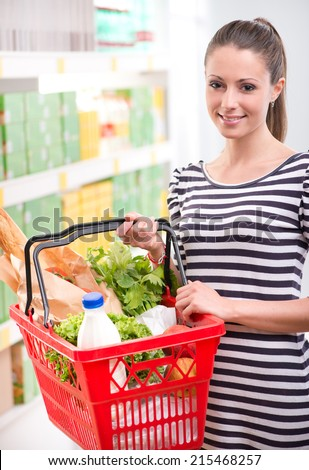 Smiling woman at supermarket with full shopping basket and shelves on background. - stock photo