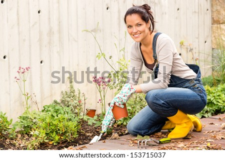 Smiling woman autumn gardening backyard housework hobby - stock photo