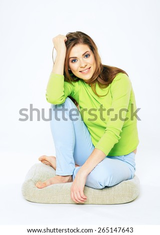 Smiling woman casual dressed sitting on a floor. Isolated portrait of smiling female model. Isolated. - stock photo