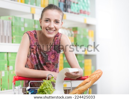 Smiling woman checking a long receipt and leaning to a full shopping cart at supermarket. - stock photo