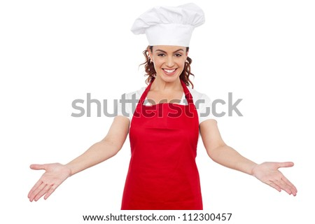 Smiling woman chef welcoming you to her workplace. Isolated over white background - stock photo