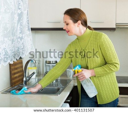 Smiling woman cleaning furniture in kitchen  - stock photo