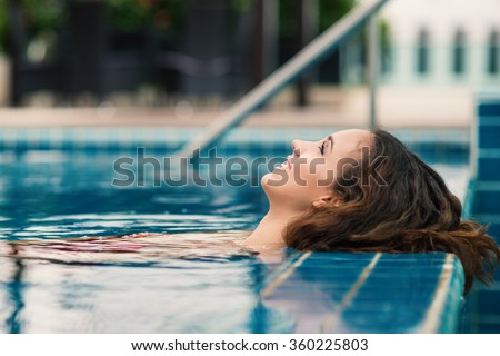 Smiling woman close up portrait in swimming pool. - stock photo