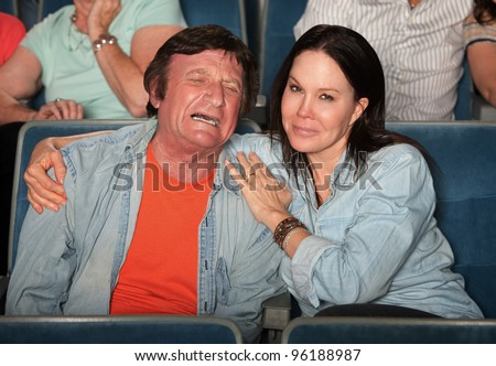 Smiling woman consoles crying man in theater - stock photo
