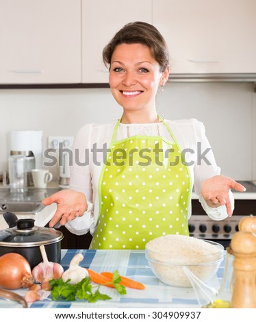 Smiling woman cooking rice at the home kitchen  - stock photo