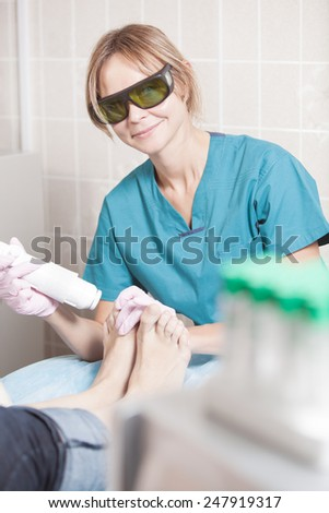 Smiling woman cosmetician in safety glasses working with laser during foot treatment - stock photo