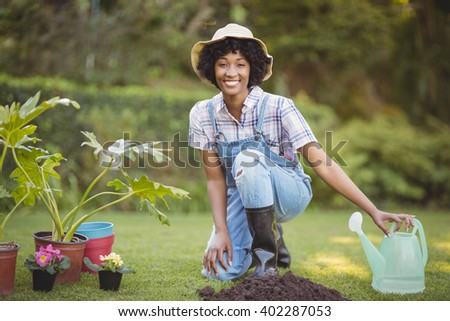 Smiling woman crouching in the garden looking at the camera - stock photo