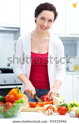 Smiling woman cutting vegetables at kitchen - stock photo