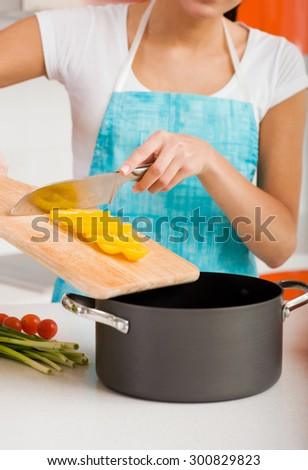 Smiling woman cutting vegetables in modern kitchen interior  - stock photo