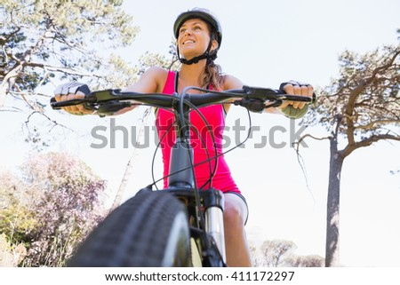 Smiling woman cycling in the countryside - stock photo
