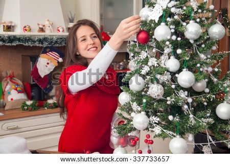 Smiling woman decorating Christmas tree at home and preparing for winter holidays. - stock photo