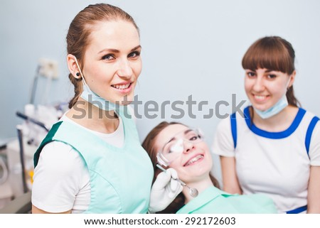 Smiling woman dentist and patient with dental braces and assistant on a background. Consultation after successful treatment in dentist office. Portrait of handsome doctor - stock photo