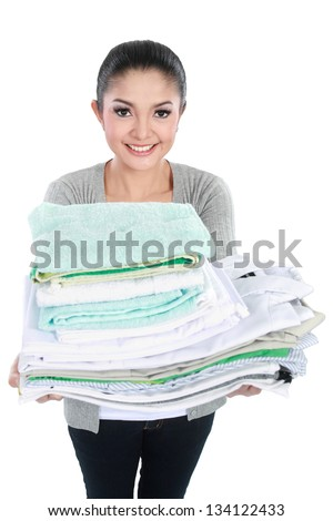 smiling woman doing a housework holding stack of clean clothes - stock photo