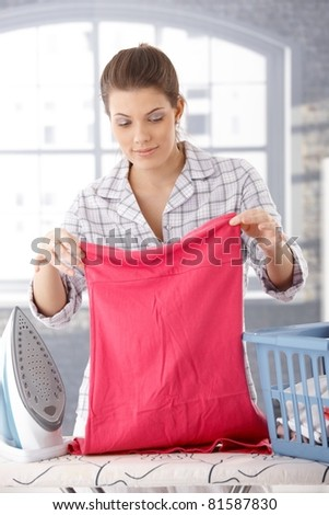 Smiling woman doing housework, ironing laundry at home.? - stock photo