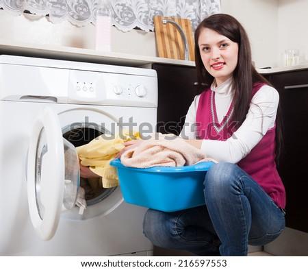 Smiling  woman doing laundry with washing machine - stock photo