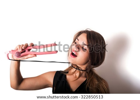 Smiling woman dressing hair with straightener - stock photo