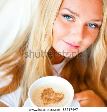 Smiling woman drinking a coffee lying on a bed at home or hotel. Heart shape illustrated on coffee foam. Horizontal shot. Model is looking to the camera. Lots of Copyspace. - stock photo