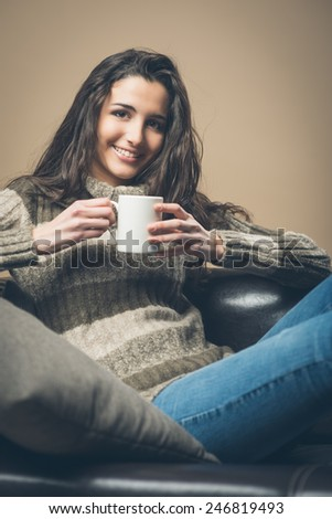 Smiling woman drinking an hot drink sitting on a sofa - stock photo