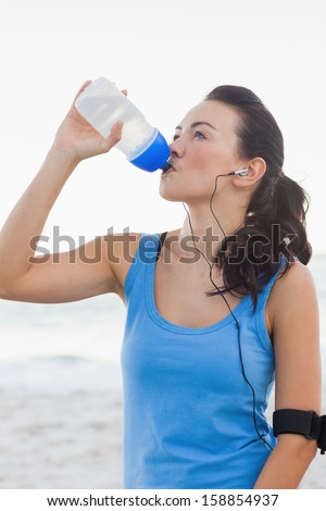 Smiling woman drinking bottled water after doing sports at the beach - stock photo