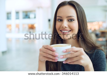 Smiling woman drinking coffee in the morning at restaurant soft focus. Closeup portrait of a pretty young lady - stock photo