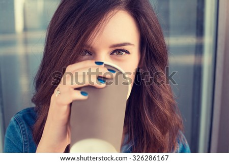 Smiling woman drinking coffee outdoors holding paper cup  - stock photo
