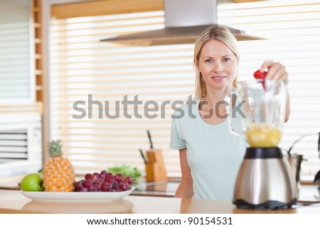 Smiling woman dropping strawberry into the blender - stock photo