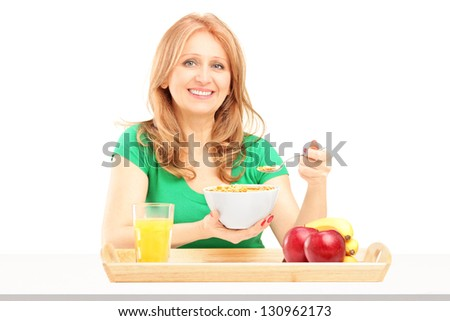 Smiling woman eating cereals and fruit for breakfast isolated on white background - stock photo