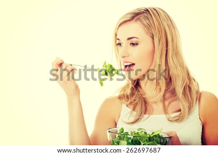 Smiling woman eating healthy salat - stock photo