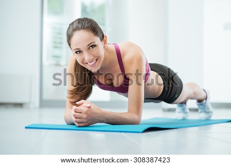 Smiling woman exercising at the gym on a mat, fitness and workout concept - stock photo