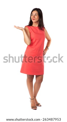 Smiling woman full length portrait isolated on white background presenting. Salmon dress. - stock photo