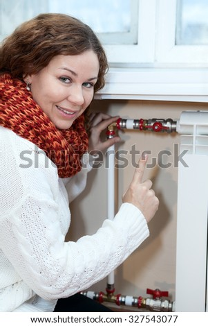 Smiling woman gesturing when turning thermostat on central heating radiator - stock photo