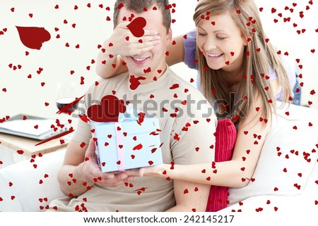 Smiling woman giving a present to her boyfriend against love heart pattern - stock photo