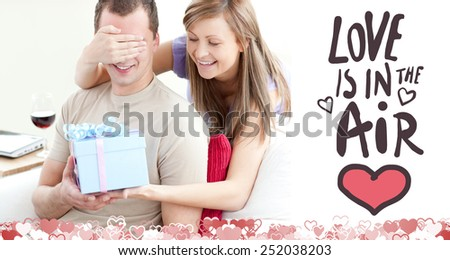 Smiling woman giving a present to her boyfriend against love is in the air - stock photo