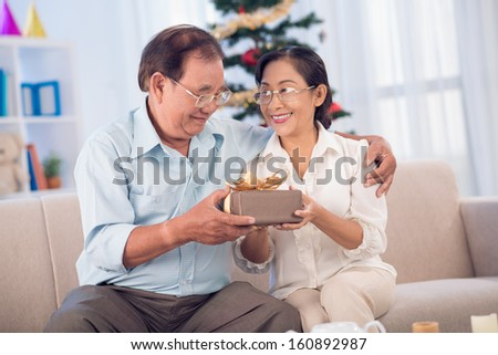 Smiling woman giving a xmas present to her hubby - stock photo