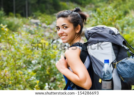 Smiling woman going to a trip in the forest. - stock photo